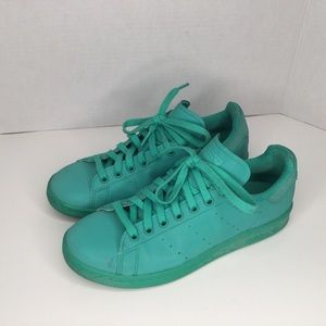 Adidas Stan Smith neon teal sneakers.